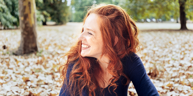 web3-woman-smile-confident-fall-leaves-park-shutterstock_1171004236